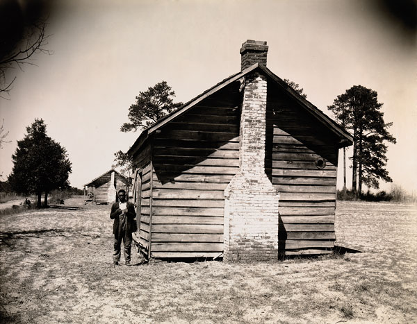Foto Walker Evans, Man Posing for Picture in Front of Wooden House, 1936