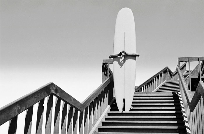 Foto Dennis Stock, Man holding a surfboard on beach steps. Corona del Mar, California, 1968